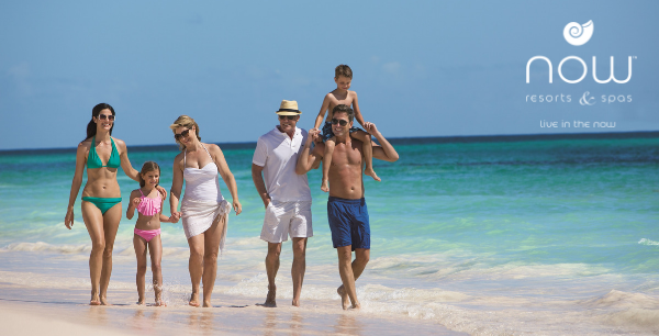 A multigenerational family walks a white sand beach next to the blue ocean.