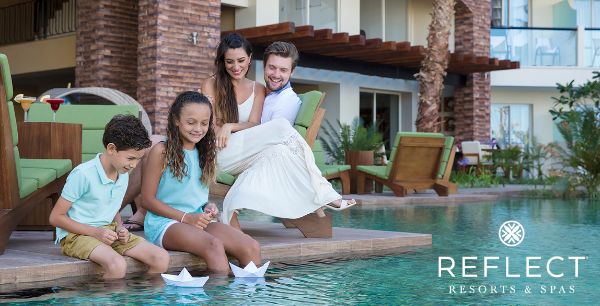 A family of four enjoys the poolside with paper boats.