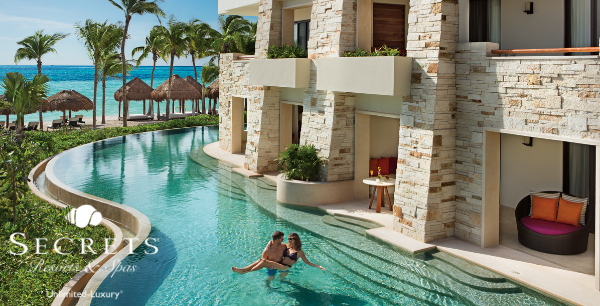 A couple enjoys their swim-up room with the beach and ocean behind them.