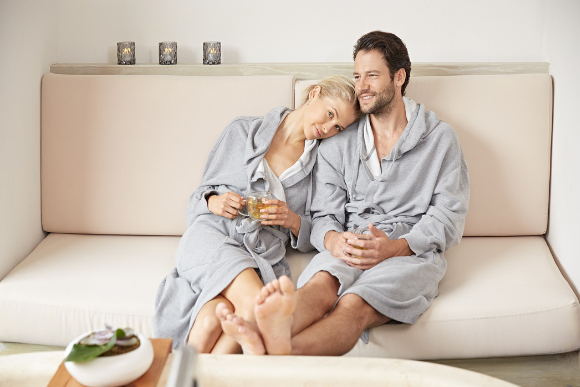 A woman rests her head on her boyfriend's shoulder as she holds a cup of tea in spa robes.