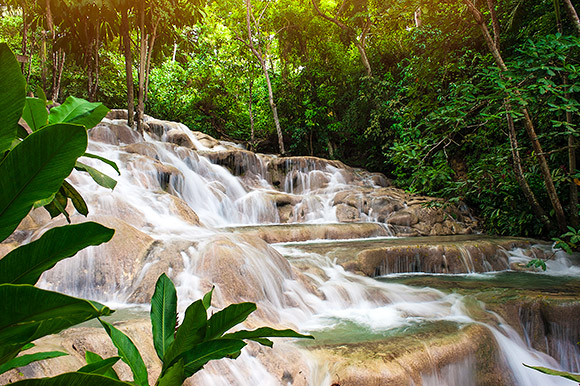 Rushing water flows over several layers of the Dunn's River Falls.